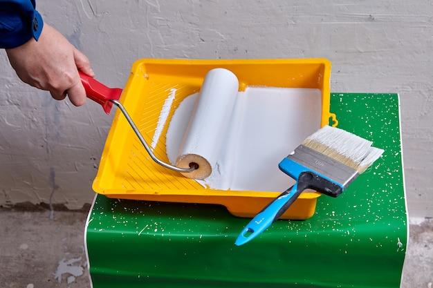 Художник с малярным валиком в руке будет красить стены с помощью рабочих инструментов и кисти во время ремонта.