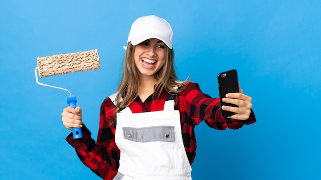 Painter woman on isolated blue making a selfie
