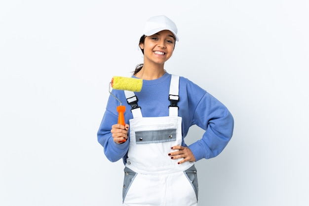 Painter woman over isolated white posing with arms at hip and smiling