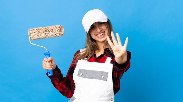 Женщина художника над изолированной голубой стеной счастливая и подсчитывающ 4 с пальцами