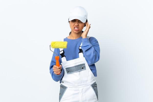 Женщина художника над изолированной белой стеной с головной болью