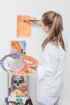 Художник работает с живописью в студии