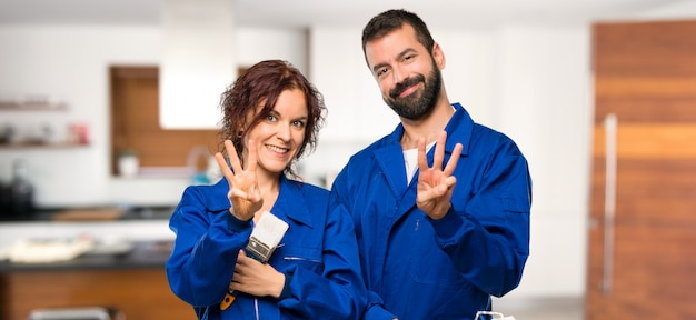 Painters happy and counting three with fingers in house