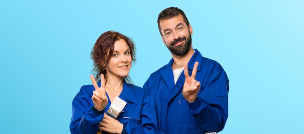 Painters happy and counting two with fingers on colorful background