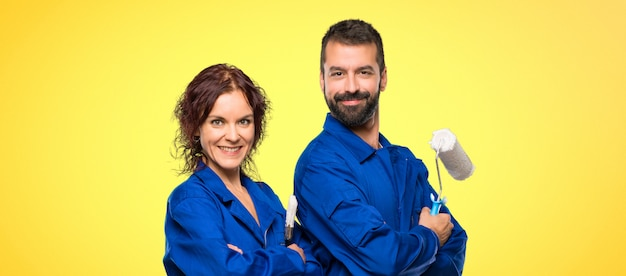Painters keeping the arms crossed in lateral position while smiling on colorful background