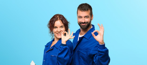 Painters showing an ok sign with fingers on colorful background