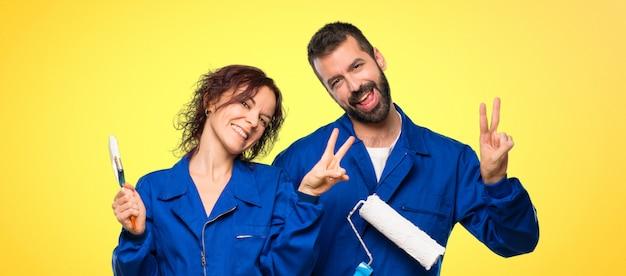 Художники улыбаются и показывают знак победы обеими руками на красочный фон Premium Фотографии