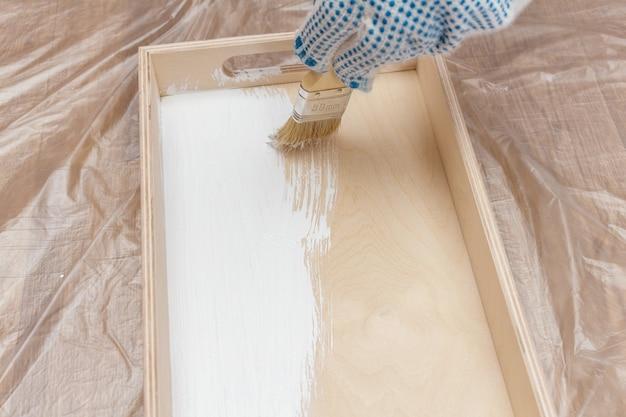 白いペンキで木製のトレイの盆を塗る