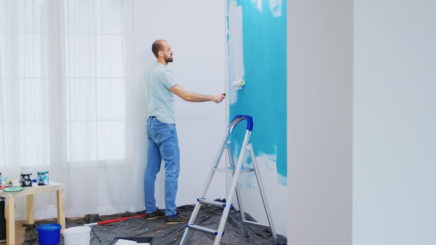 Painting apartment wall with white paint using roller brush. handyman renovating. apartment redecoration and home construction while renovating and improving. repair and decorating.