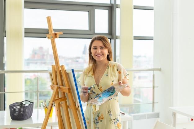絵画美術の授業。描画コース。スキルの想像力とインスピレーション。イーゼルで絵を描く魅力的な学生の女の子。