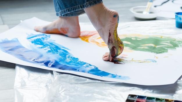 絵画美術学校。カラフルな抽象的なアートワークを作成し、紙の上を歩くアーティストの足のクローズアップ。