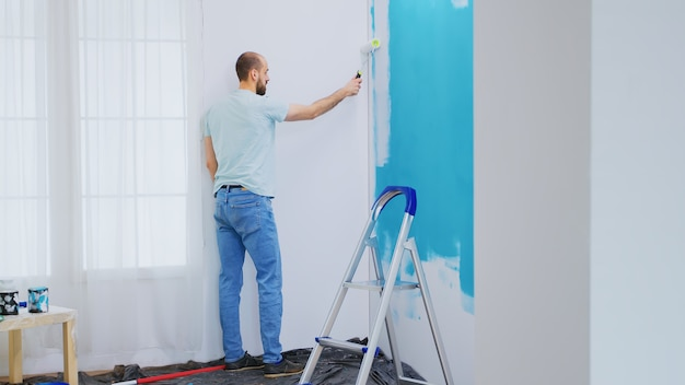Painting blue wall with white paint using roller brush during home renovation. handyman renovating. apartment redecoration and home construction while renovating and improving. repair and decorating.