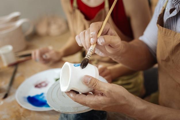 페인팅 브러쉬. 그의 일을 마무리하는 점토 냄비를 장식하면서 그림 붓을 들고있는 남성 포터