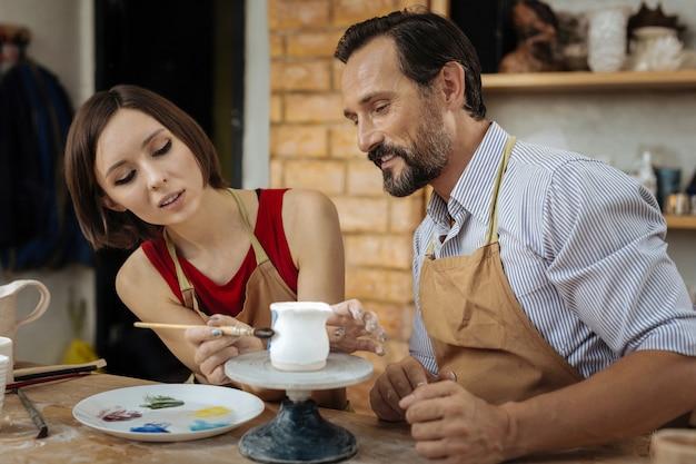 그림 점토 냄비. 남편 근처에 앉아 작은 항아리 그림 갈색 앞치마를 입고 검은 머리 여성 도공