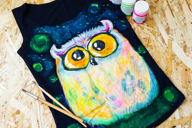 Painting concept. a painted owl on a black t-shirt.