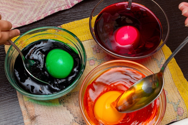 Painting, dying colorful eggs for easter in glass dish