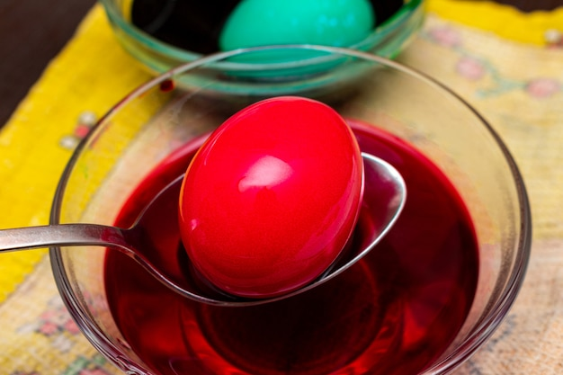 Painting, dying red easter eggs in glass dish