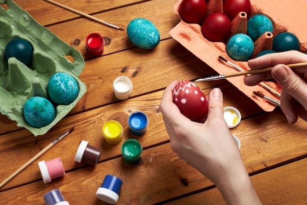 卵を塗る。女性の手はイースターの日に卵を描きます。イースターの準備。
