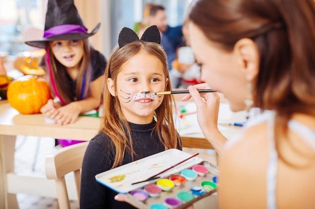 顔を塗る。猫のハロウィーンの衣装を着ている小さな暗い目の女の子のための暗い髪の幼稚園の先生の絵の顔
