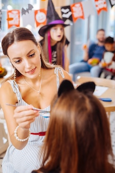 Painting faces. dark-haired teacher wearing white striped dress painting faces of children getting ready for halloween