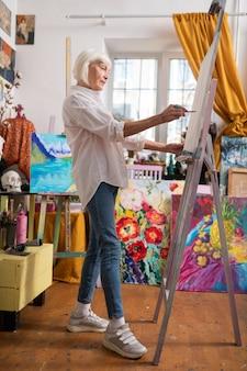 ワークショップでの絵画。ワークショップでインスピレーションを得た絵画を感じているジーンズとスニーカーを身に着けている年配のアーティスト