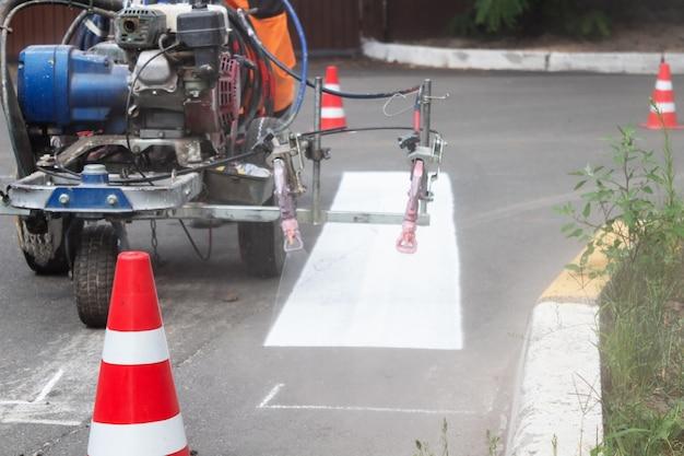 Окраска проезжей части пешеходного перехода малярной машиной. дорожные работы.