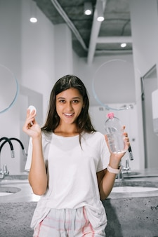 화장실에서 목화 패드와 함께 아름다운 젊은 여성의 그림
