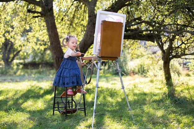 Картина на холсте с использованием мольберта в зеленом летнем саду при ярком солнечном свете. кавказская маленькая девочка художника, одетая в джинсовое платье, рисует на холсте в городском парке или саду.