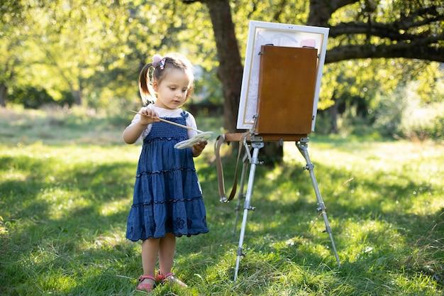 Живопись на мольберте на природе на природе. маленькая милая талантливая возбужденная девочка-художник, рисующая картину на холсте, держа палитру и кисть и выбирая цвет краски.