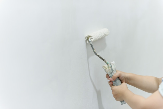 Painting out a white wall with a paint roller with white paint.