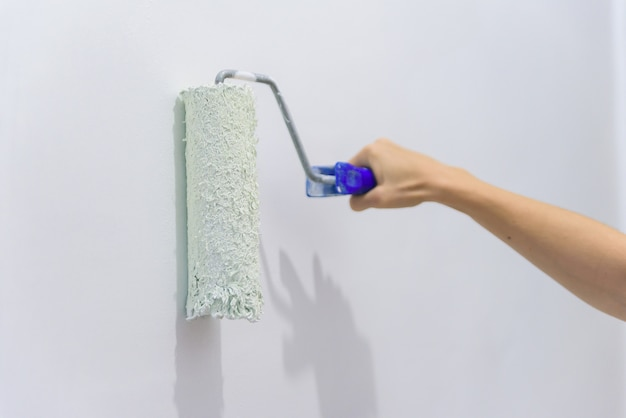 Painting out a white wall with a paint roller with white paint. Premium Photo