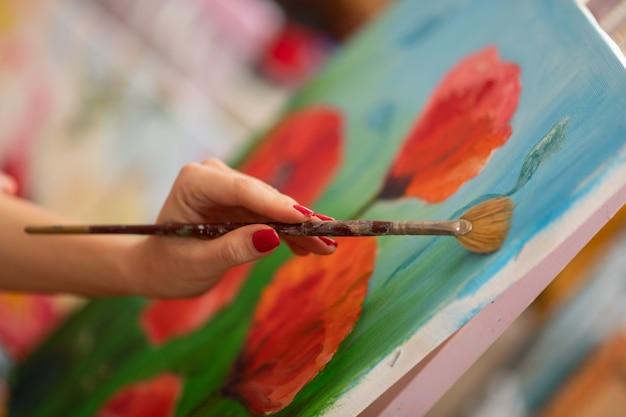 ポピーの絵。絵筆と絵のポピーを保持している赤い釘でアーティストのクローズアップ