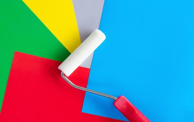 赤、緑、青、黄色の背景にローラーをペイント
