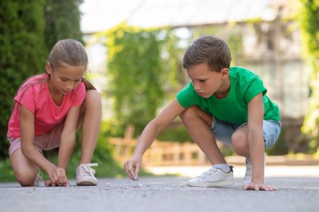 Картина. серьезные сосредоточенные мальчик и девочка младшего школьного возраста рисуют мелками в парке в теплый день