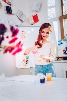 페인팅 스튜디오. 수채화를 준비하는 그녀의 페인팅 스튜디오에 서있는 유망한 창조적 인 예술가