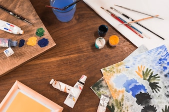 Painting supplies and pictures on table