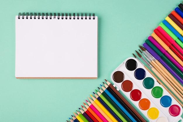 Концепция принадлежности для рисования. вверху над сверху вид фото красочных канцелярских принадлежностей и альбомов, изолированных на бирюзовом фоне с copyspace