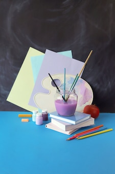 Painting teaching supplies books apple on table against chalkboard background back to school