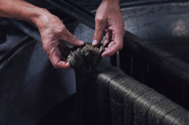 Painting threads and yarns male hands paint the cloth in the trough