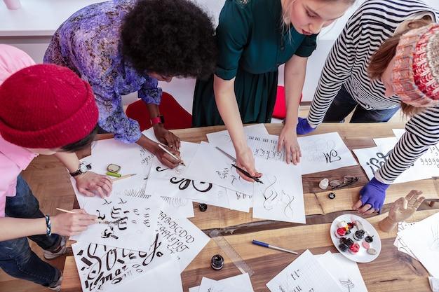一緒に絵を描く。一緒に絵を描く芸術部門の4人の創造的な才能のある学生の上面図