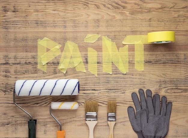 Инструменты для рисования на деревянном столе со словом paint из малярной ленты. ремонт дома или квартиры.