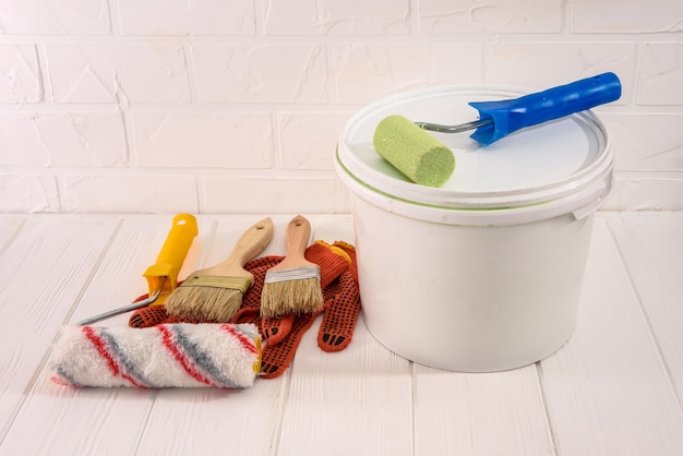Painting tools with bucket on wooden table