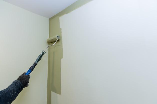 컬러 페인트로 리노베이션하기 위해 롤러를 사용하는 페인팅 벽 작업자