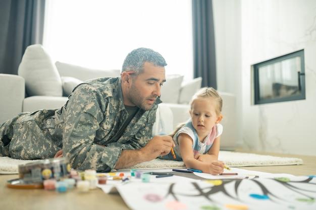 딸과 그림. 그의 귀여운 딸과 함께 가계도를 그리는 잘 생긴 성숙한 군인