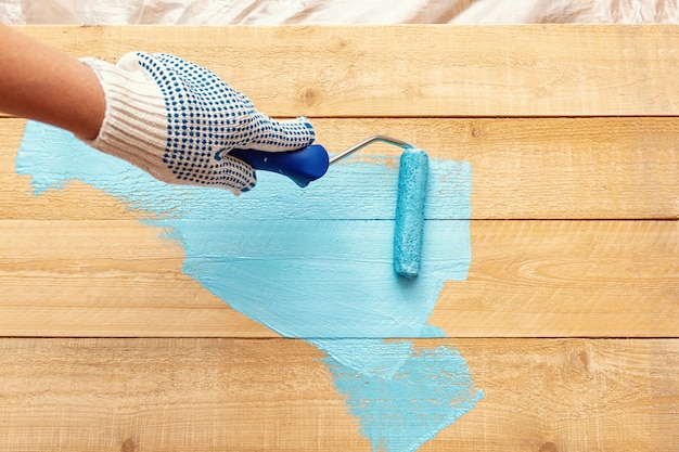 Painting with the paint roller blue color paint on the wooden