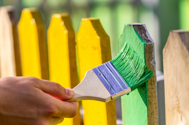 Painting a wooden fence with green paint