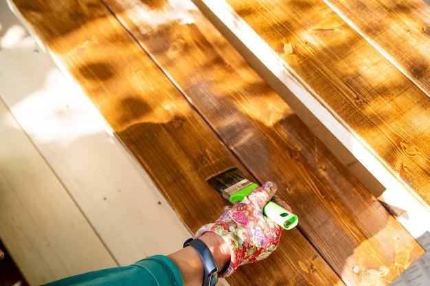 Покраска деревянной террасы защитным лаком, рука в защитных перчатках, держащая кисть, покраска деревянных поверхностей, реставрация садовой мебели.