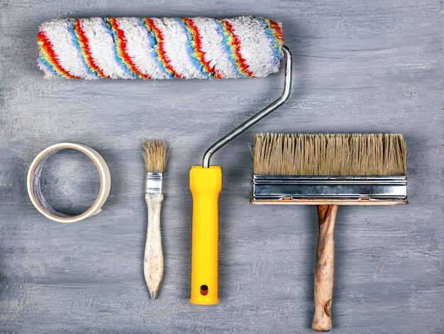 Концепция малярных работ. набор инструментов для покраски и ремонта стен. валик и кисть на сером фоне.