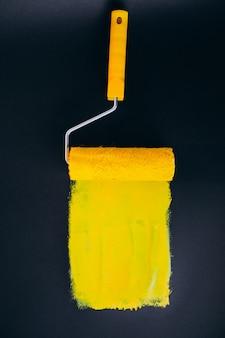 黄色の塗料で黒の背景に分離された修理用paintroller