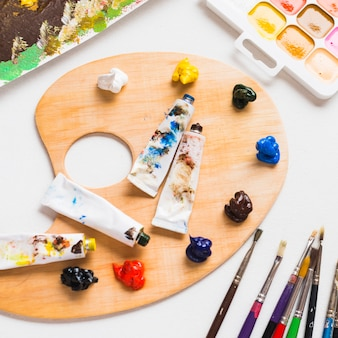 Paints and brushes near wooden palette